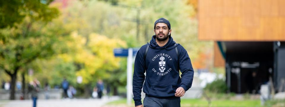 Man wearing U of T shirt walking on campus