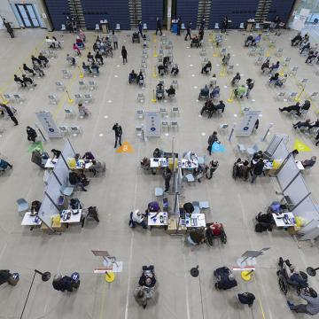 Overhead shot of chairs, physically distanced, in gymnasium, with people sitting in them after being vaccinated. Also seen are vaccination stations where people are receiving their dose.
