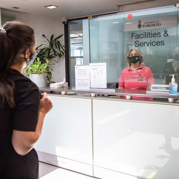 Woman in mask approaching desk with plexiglas and person behind it wearing a mask
