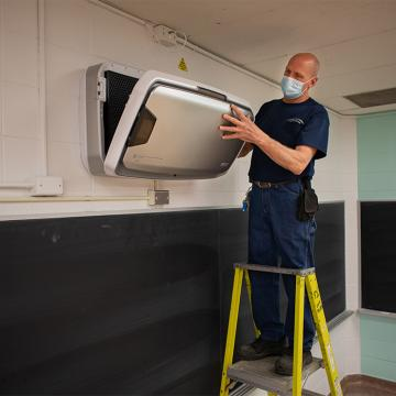 Man wearing blue shirt, jeans and blue paper face mask standing on step ladder in classroom installing an air purification unit on a brick wall above a chalkboard.