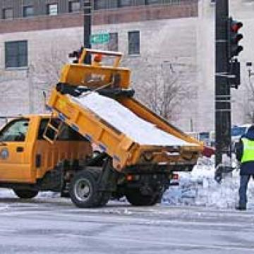 Workers manually spreading salt from a salt truck in Milwaukee, Wisconsin.