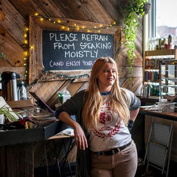 "Sasha Steinberg standing by counter in restaurant, display of baked goods and four rows of shelves holding beverages behind her. Sign on counter says ""Hot mulled cider"" and chalkboard behind her on wall reads: Please refrain from speaking moistly (and enjoy your day)."