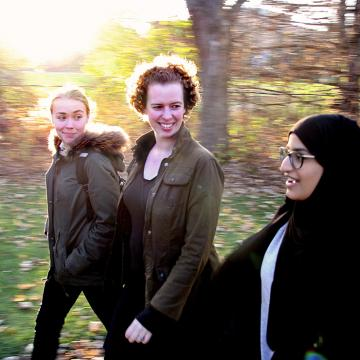 Fiona Rawle walking with two students on campus near trees
