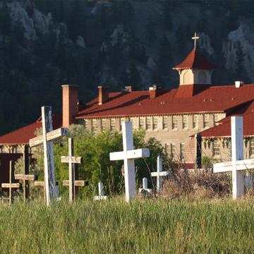 Brick building with red roof, cross on top, in foreground are white, weathered wooden crosses in a field