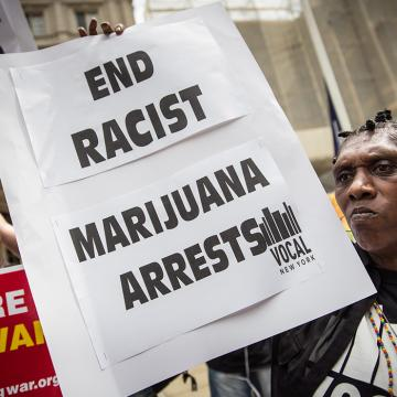 protestor holds sign that says end racist marijuana arrests. Sign in background held by another protestor reads No more biased policing.