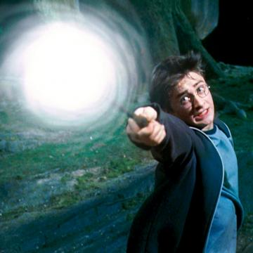 Movie still showing frightened Harry Potter casting a spell. The tip of his wand is engulfed in a swirling white light.