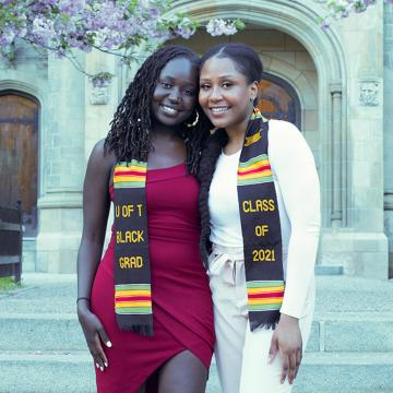 Two women standing in front of stone building wearing a black kente cloth that says U of T Black Grad Class of 2021