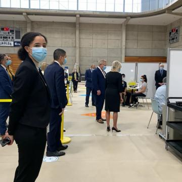 Reem El-Ajou standing in clinic, wearing a black blaze, black pants and blue surgical face mask. In the background are physically distanced chairs, hand sanitizer and Mississauga Mayor Bonnie Crombie and Ontario Premier Doug Ford  along with other special guests in blue suits touring the clinic