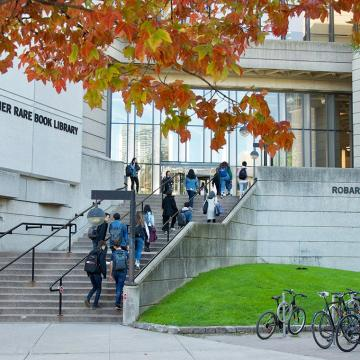 Photo of Robarts Library, grey concrete building with wide staircase leading up to glass entrance, with students walking up the stairs.