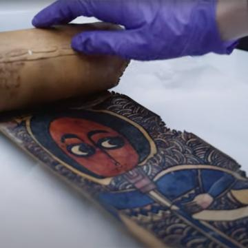 Hand wearing latex-like glove unrolling a scroll about a hands-width with colourful image of a person with round head, large eyes, and a blue robe