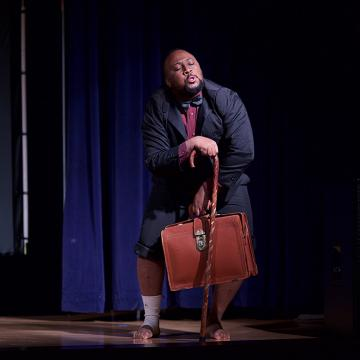 Actor standing on stage in a blue suit, pant legs rulled up, wearing a bow tie and leaning on a cane while holding a battered briefcase