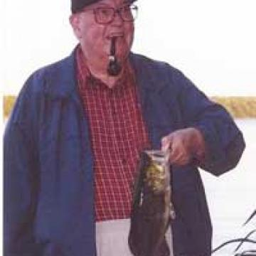 Professor Emeritus Peter Silcox smoking a pipe and holding a fish by the gills.