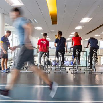 Row of people on ellipticals with person running in foreground