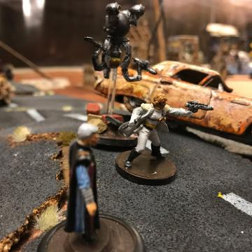 Photo of three miniature humanoid figures on an apocalyptic tabletop scene scattered with debris and overturned cars.