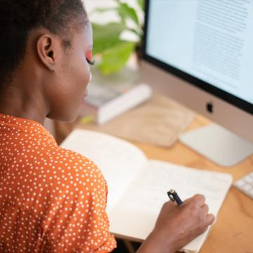 Woman in front of computer screen writing in notebook