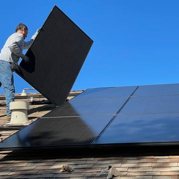 A man stands on a roof installing solar panels
