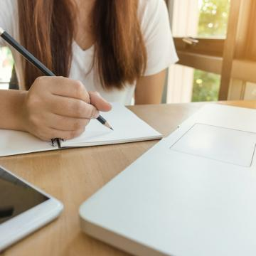 Woman holding pencil over open notebook with open laptop on front of her