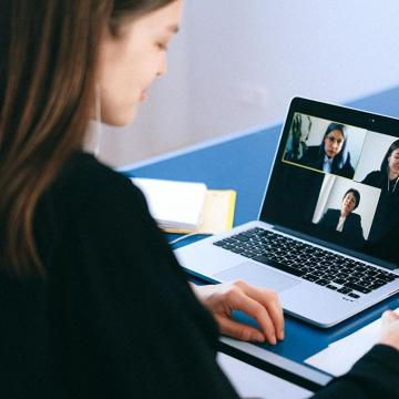 Woman in front of laptop on video call with three others shown on screen