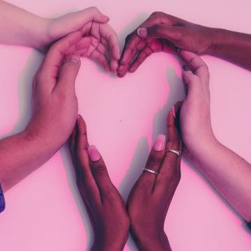 Three pairs of hands coming into the middle of the frame to create a heart against a white backdrop