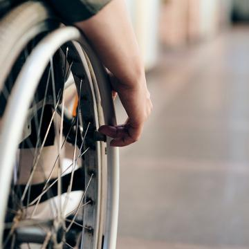 Close up of wheelchair wheel with hand on it