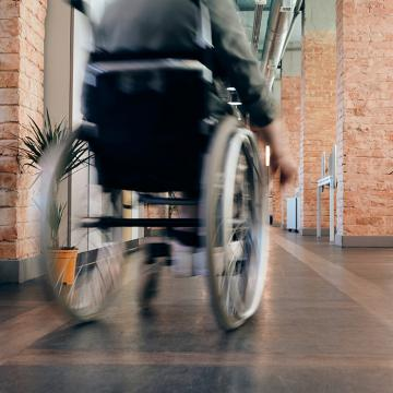 Individual in wheelchair moving away from camera in hallway with brick pillars on either side