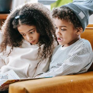 Two children sitting on couch reading a book together