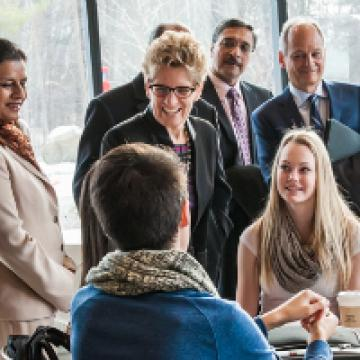 Premier Wynne greets students sitting at a table