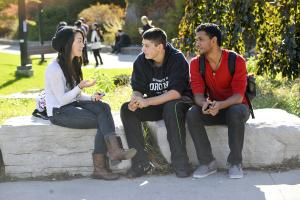 three students chatting while sitting outside on rocks
