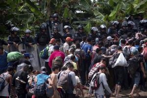 A new group of Central American migrants walk past Mexican Federal Police