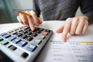 Closeup photo of financial spreadsheets and hands using a calculator and