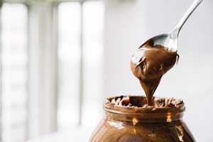 Photo of a jar and a spoon heaped with chocolate spread.