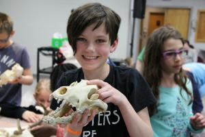 Young girl holding an animal skull and smiling