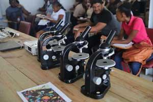 Close-up photo of three microscopes on a table with students in the background