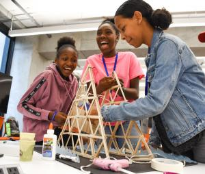 Three young students laugh as they build a pyramid from wooden popsicle sticks.