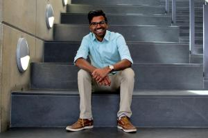 Daniel Jayasinghe sits on the stairs