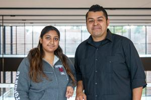 From left, Aarthi Thota wearing a grey hoodie standing next to Jerry Flores, wearing a deep blue button down shirt. Both are standing in front of glass windows.