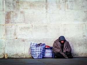 A homeless man sits on the ground. He is bundled in a blanket. Two large bags are beside him.