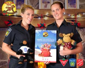 Peel Police constables hold stuffed animals in front of Toys for Tots logo