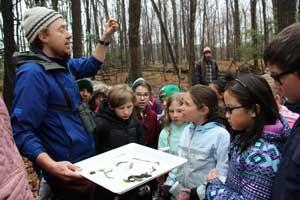 Associate professor of biology Marc Johnson stands in a forest setting surrounded by a group of attentive school children.