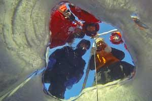 Four researchers look down through a hole in lake ice to underwater camera
