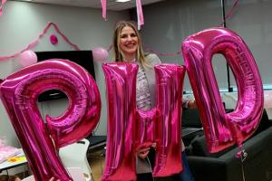 """Sasha Weiditch holds pink balloons spelling out """"P H D"""""""