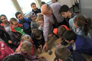 Ulrich Krull shows a crowd of elementary students a piece of meteorite