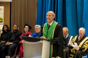 Ulrich Krull speaks at podium during installation