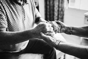 A black and white close-up photograph of an elderly couple holding hands.