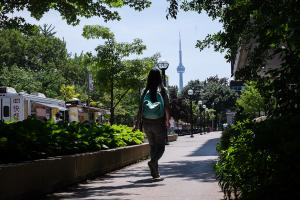 female student with backpack walking along sidewalk with CN Tower in background