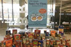 Stacks of canned food on a table with a sign that reads: UTM Library Food for Fines