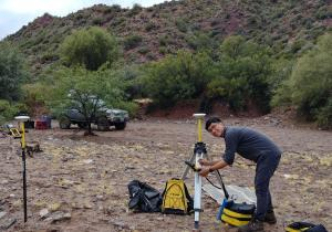 Jeremy Rimando sets up survey equipment in a rocky landscape.
