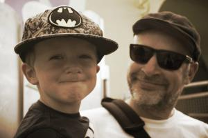 Man with hat and sunglasses holding a smiling child wearing a baseball hat