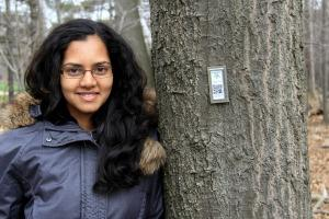 Woman with long dark hair leaning against a tree with a QR code tag