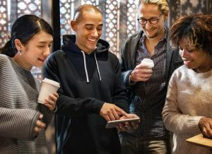 A group of college students smile as they look at a mobile phone.